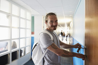 Portrait of man opening door while students standing in corridor at university - MASF01430