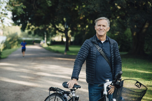 Portrait of smiling senior man with bicycle standing in park - MASF01439