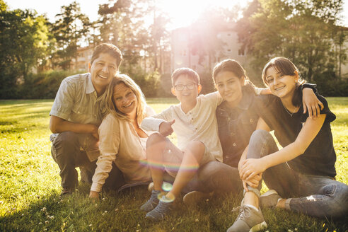 Portrait of smiling family sitting on grassy field at park - MASF01445