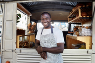 Portrait of smiling mid adult male owner standing outside food truck - MASF01451