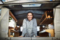 Portrait of smiling mid adult owner standing in food truck - MASF01454
