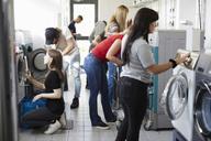 Multi-ethnic university students doing laundry at laundromat - MASF01499