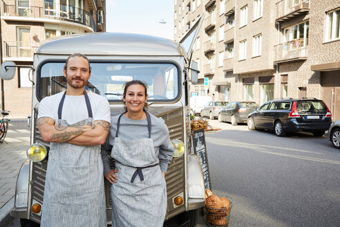 Portrait of confident male and female owners standing in front of food truck parked on city street - MASF01523
