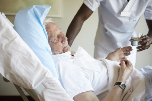 Midsection of male nurse giving drinking water to senior man in hospital ward - MASF01538