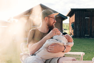 Mid adult man holding baby boy while sitting outside - MASF01547