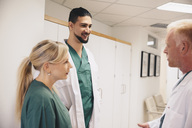 Mature doctor discussing with colleagues in hospital corridor - MASF01562