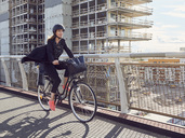 Mature woman cycling on footbridge against building - MASF01577