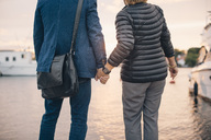 Midsection of senior couple holding hands while standing at harbor - MASF01580