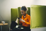 Mid adult businesswoman using smart phone while sitting on green chair at office - MASF01586