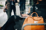 Midsection of businesswoman using laptop sitting at bus shelter seen from glass - MASF01592