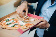 Midsection of businessman eating pizza from cardboard box in city - MASF01601