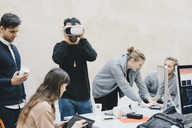 Male computer programmer using VR glasses while colleagues working in office - MASF01640