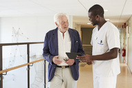 Male nurse and senior male patient discussing over digital tablet at hospital corridor - MASF01646