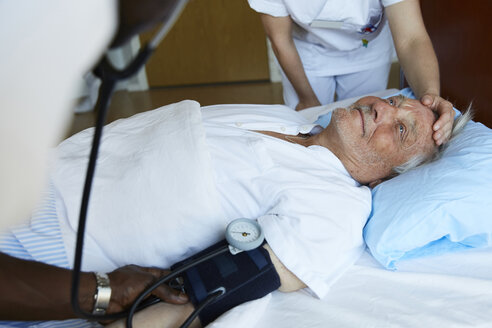 Male nurse checking blood pressure of senior man on hospital bed while colleague consoling patient - MASF01649