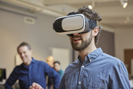 Male professional using virtual reality simulator against colleagues at creative office - MASF01652