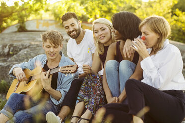 Man playing guitar while friends enjoying during summer - MASF01667