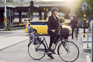 Mature businesswoman with bicycle on street in city - MASF01670