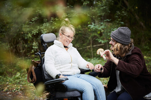 Male caretaker showing mushroom to disabled woman in wheelchair at forest - MASF01679