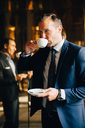 Mature businessman drinking coffee while standing against reflection of male colleague on glass - MASF01691