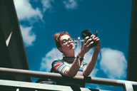 Low angle view of young woman taking selfie with mobile phone while leaning on railing against sky - MASF01713