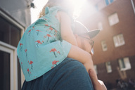 Low angle view of father carrying daughter on shoulders in city during sunny day - MASF01725