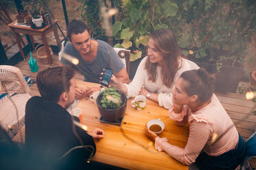 High angle view of young woman showing mobile phone to friends while sitting at table - MASF01746