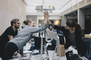 Happy female computer programmers giving high-five over desk in office - MASF01779