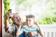 Grandfather taking selfie with grandson in porch - MASF01797