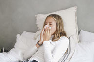 Girl blowing nose while lying on bed at home - MASF01800