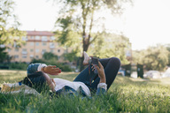 Full length of teenage girl using smart phone while lying on grass - MASF01803