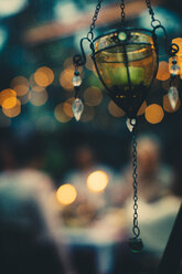 Glass decor hanging against friends sitting at dining table during garden party - MASF01806