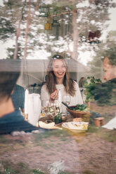 Happy young woman having lunch with friends seen through glass - MASF01812