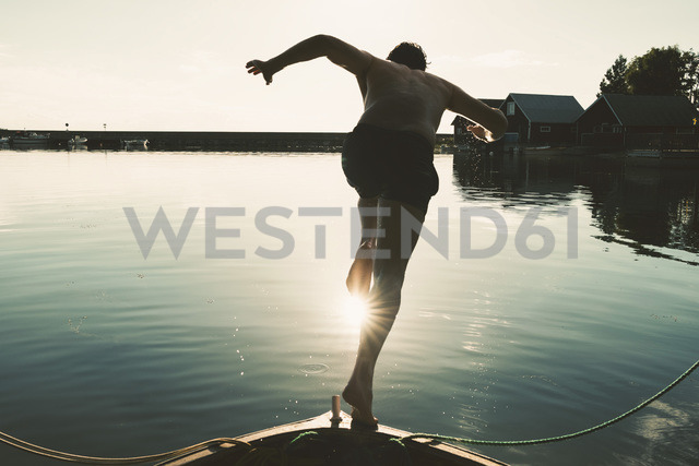 Full length of shirtless man diving into lake from boat on sunny day - MASF01824 - Maskot ./Westend61