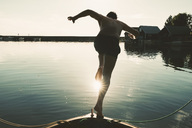 Full length of shirtless man diving into lake from boat on sunny day - MASF01824