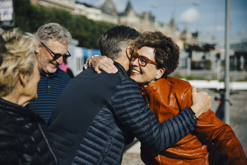 Happy senior woman embracing man by friends in city during vacation - MASF01839