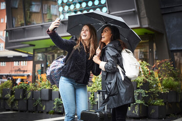 Happy friends with umbrella taking selfie through mobile phone while standing in city - MASF01842