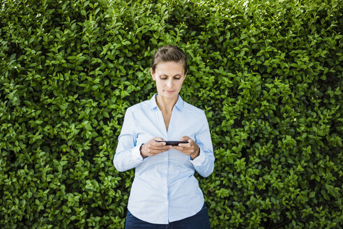 Woman standing at a hedge using cell phone - JOSF02170