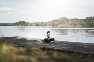 Relaxed woman sitting on jetty at a lake - JOSF02173