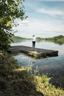 Woman standing on jetty at a lake wearing VR glasses - JOSF02176