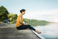 Happy woman sitting on jetty at a lake - JOSF02179