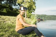 Woman sitting at a lake wearing VR glasses - JOSF02182