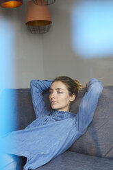 Portrait of woman wearing denim shirt relaxing on the couch - PNEF00584