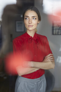 Portrait of woman wearing red blouse standing behind windowpane - PNEF00587