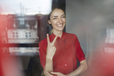 Portrait of laughing woman behind windowpane showing victory sign - PNEF00590
