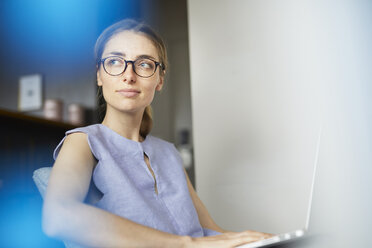 Portrait of woman wearing glasses sitting on armchair with laptop - PNEF00593