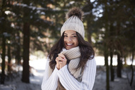 Portrait of happy young woman wearing knitwear in winter forest - ABIF00278