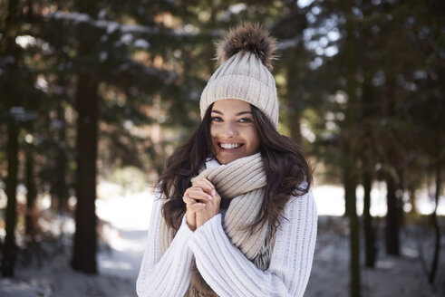 Portrait of happy young woman wearing knitwear in winter forest - ABIF00278