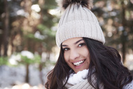 Portrait of smiling young woman wearing woolly cap in forest - ABIF00281