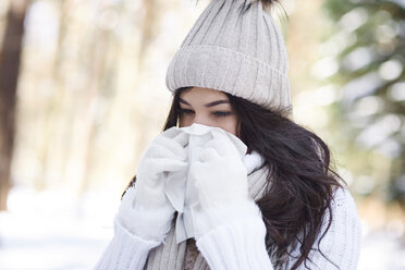 Young woman blowing nose in winter - ABIF00284