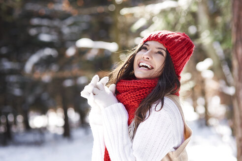 Portrait of happy young woman in winter forest - ABIF00287